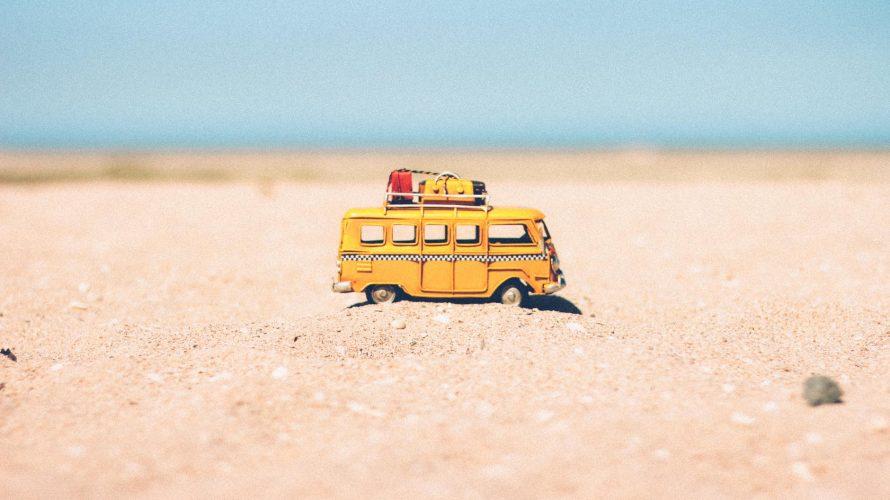 yellow die cast miniature van on brown sand